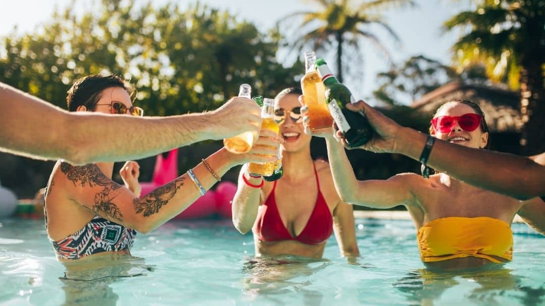 friends drinking mixed drinks in a pool