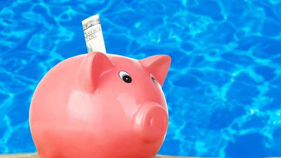 Image of a piggy bank in front of blue waters representing the next section on swimming pool financing.