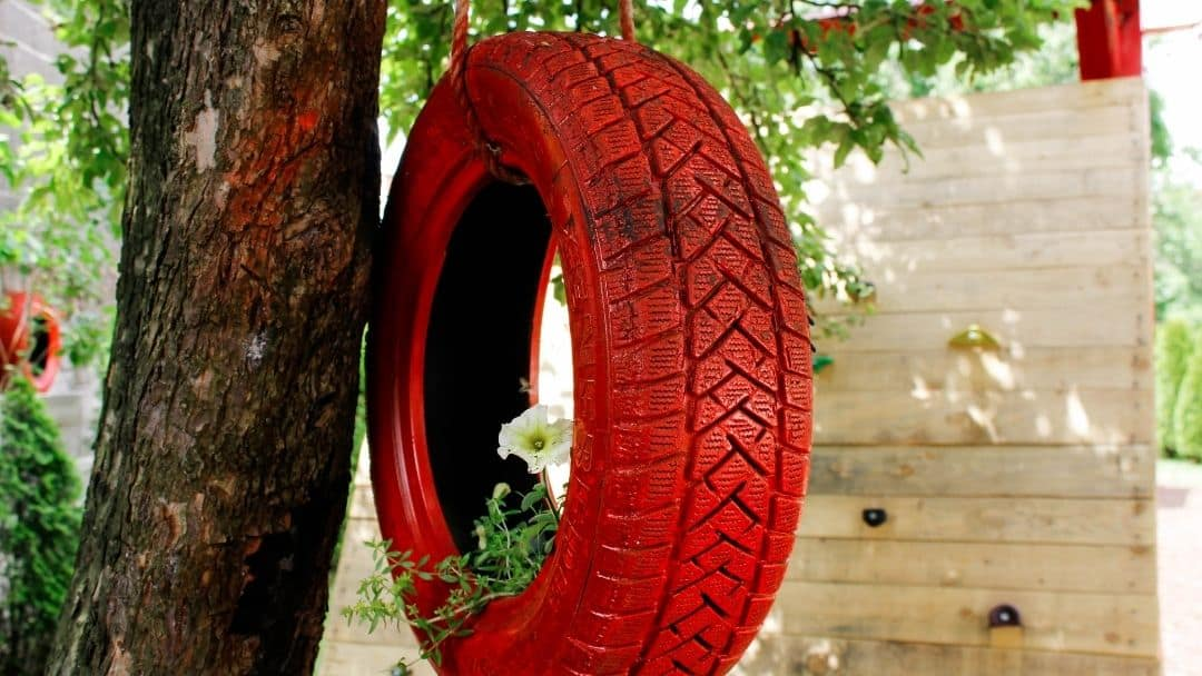 A tire painted red and hanging from a tree with flowers growing inside.